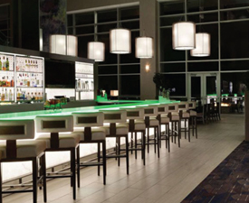 green lit bar with stools